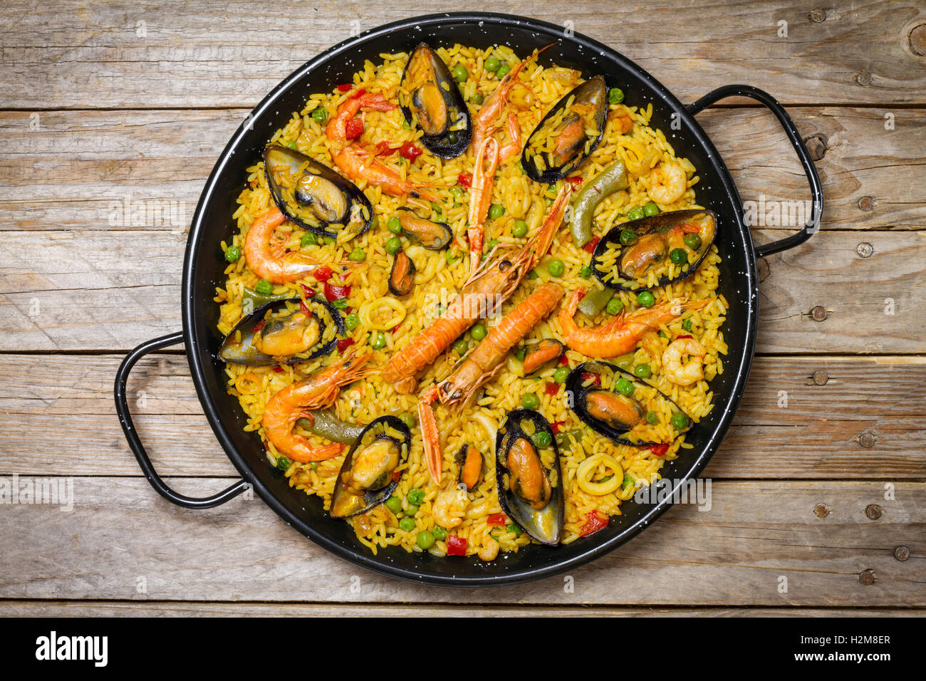 Spanish paella on an antique wooden table - Stock Image