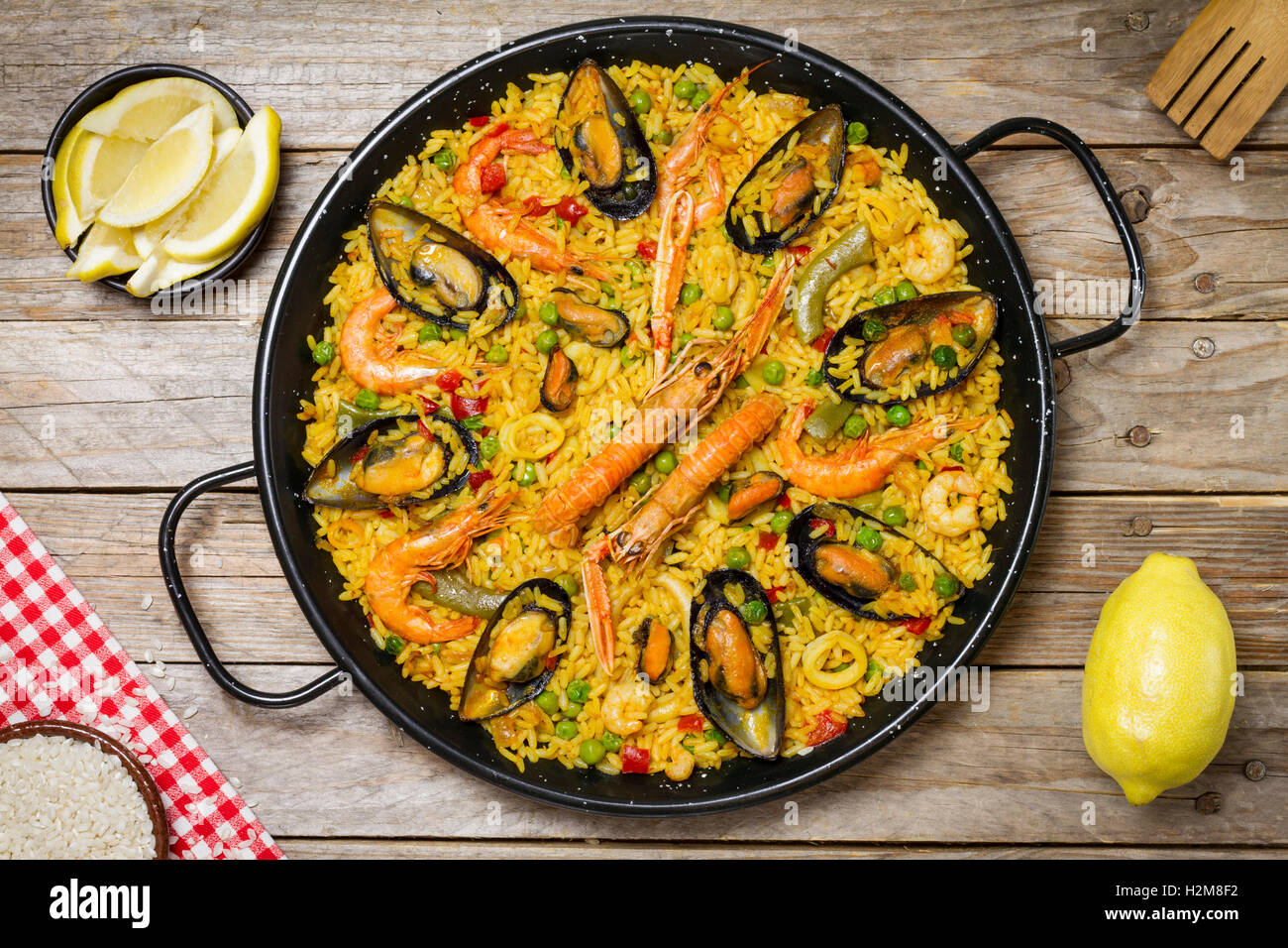 Spanish paella on a wooden table with fresh lemon and a white and red tablecloth and a wooden fork Stock Photo