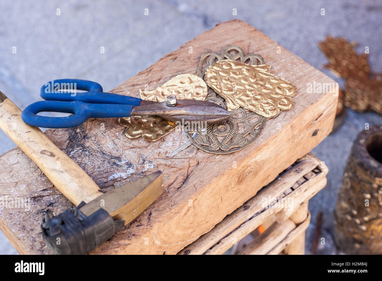 Craftsman bench with tools for engrave hamsa palm-shaped brass amulets - Stock Image