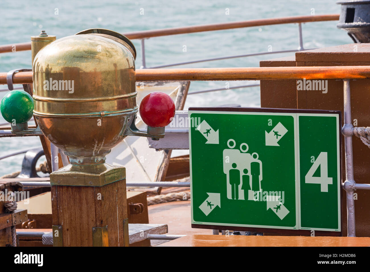 imo muster station sign and brass binnacle on the Waverley Paddle Steamer at sea on the South Coast in September - Stock Image