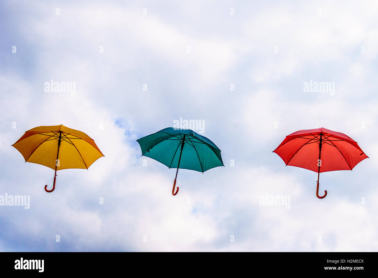Yellow Umbrella, Green Umbrella, Red Umbrella floating in the Air under Partly Blue Sky with cloudy periods. - Stock Image