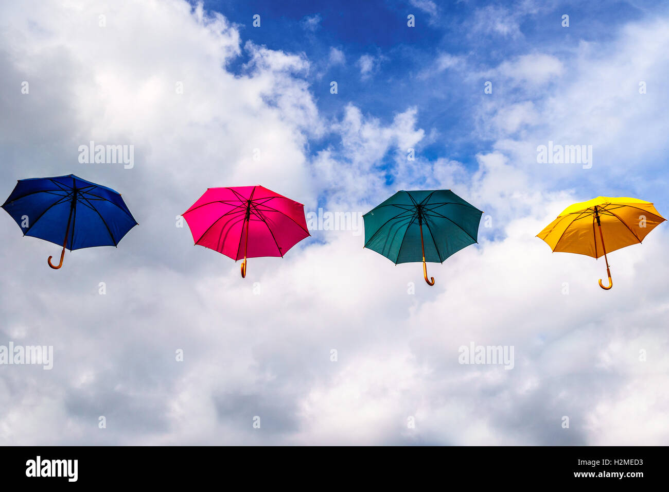 Blue Umbrella, Pink Umbrella, Green Umbrella, Yellow Umbrella floating in the Air under Partly Blue Sky and Clouds - Stock Image