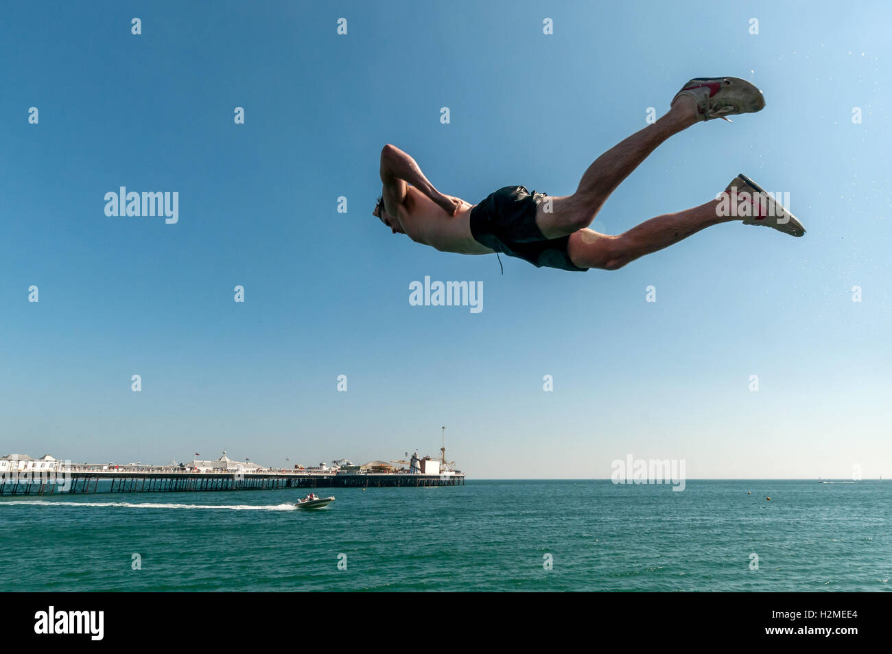 Young people jumping into the sea from the Banjo Groyne on Brighton beach - Stock Image