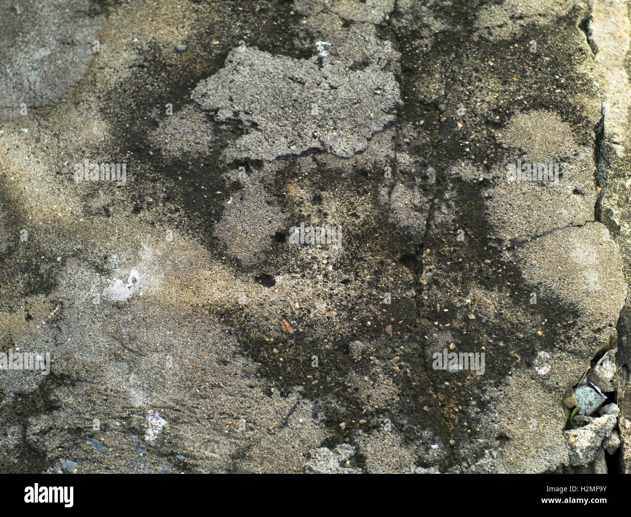 cracked and grainy concrete surface with stains - Stock Image