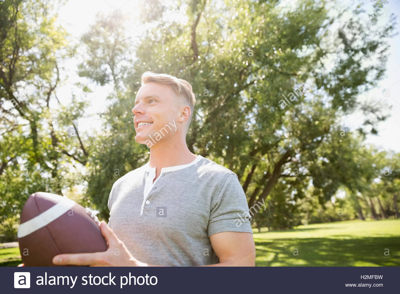 Smiling man playing football in sunny summer park Stock Photo