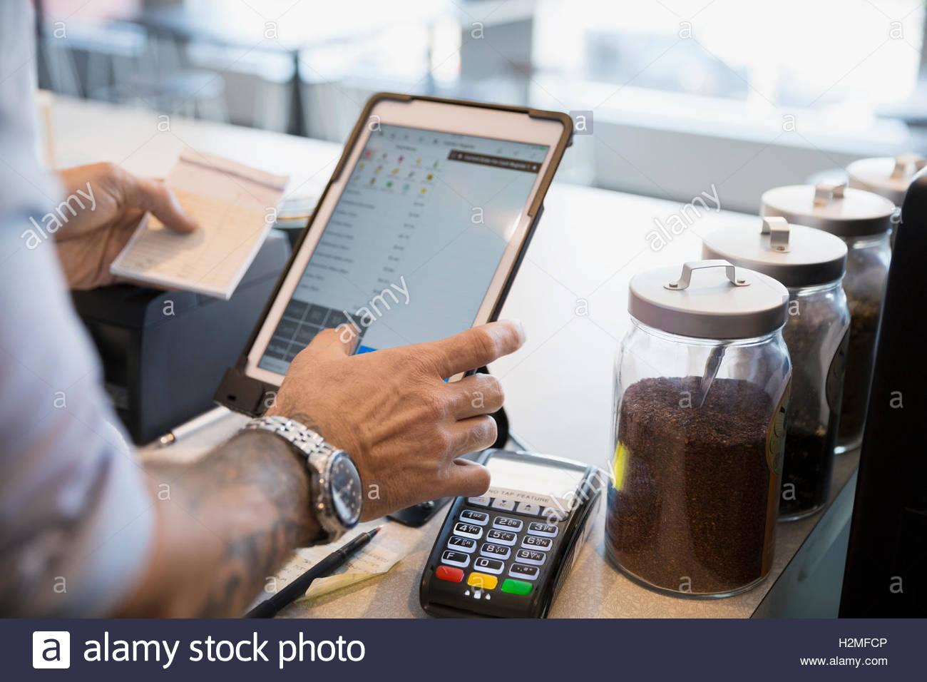 Male cafe owner holding check using digital tablet at cash