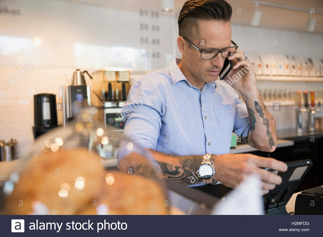 Male cafe owner talking on cell phone at cash register - Stock Image