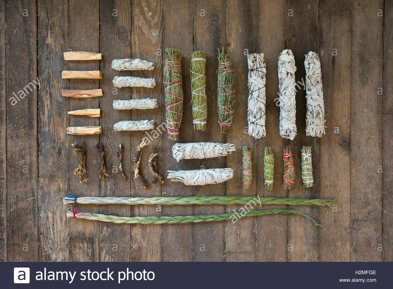 Overhead view smudge sticks and patio santo on wooden floor - Stock Image
