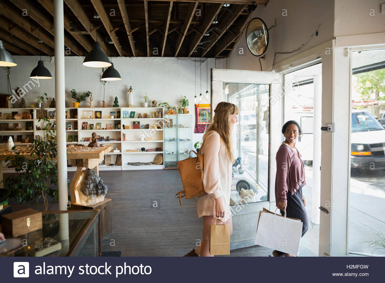Women friends leaving new age shop with shopping bags - Stock Image