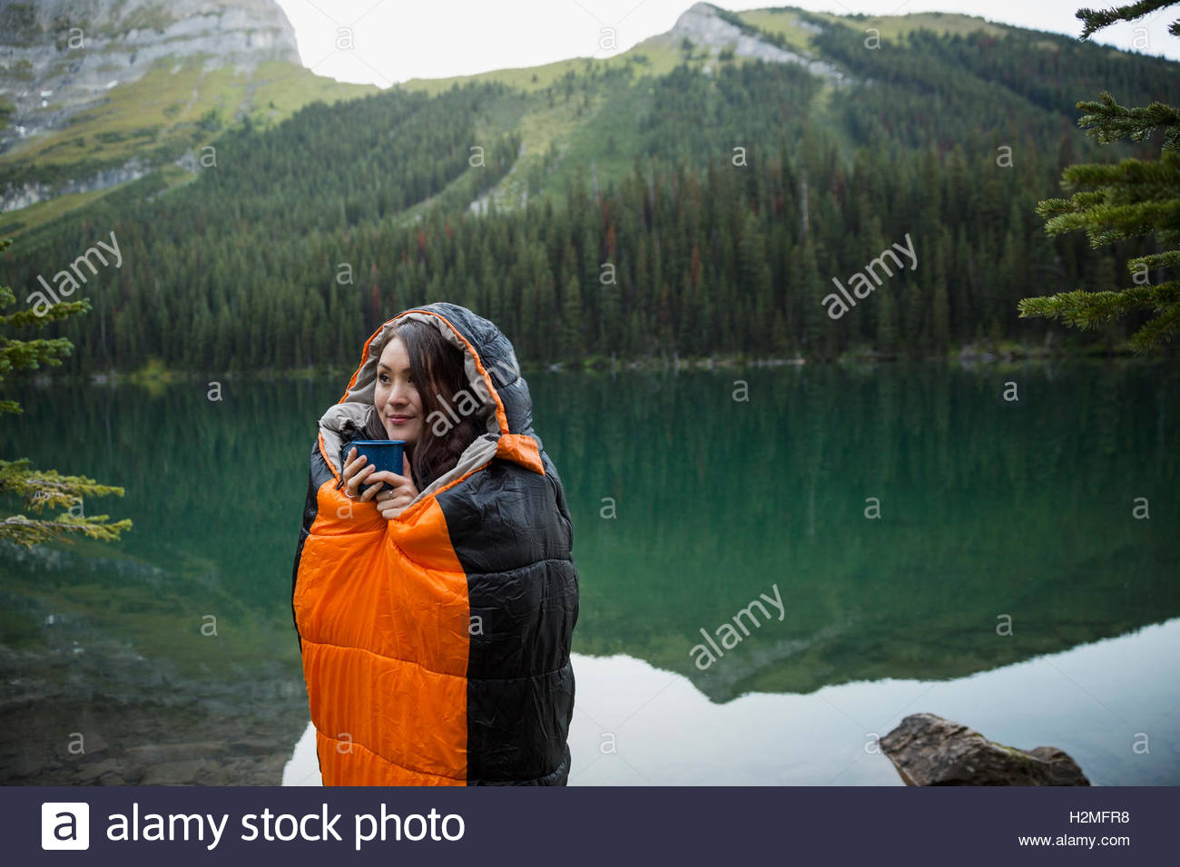 Woman standing in sleeping bag at remote lakeside - Stock Image