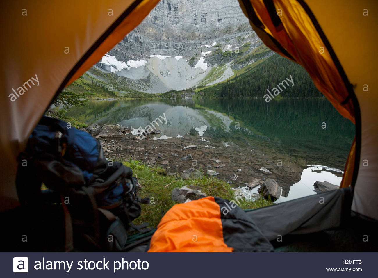 View of mountain and tranquil lake from inside of camping tent - Stock Image