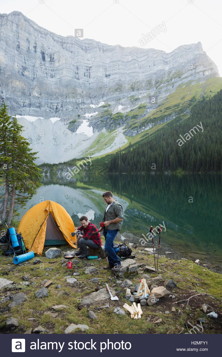 Male friends camping at remote mountain lakeside campsite - Stock Image