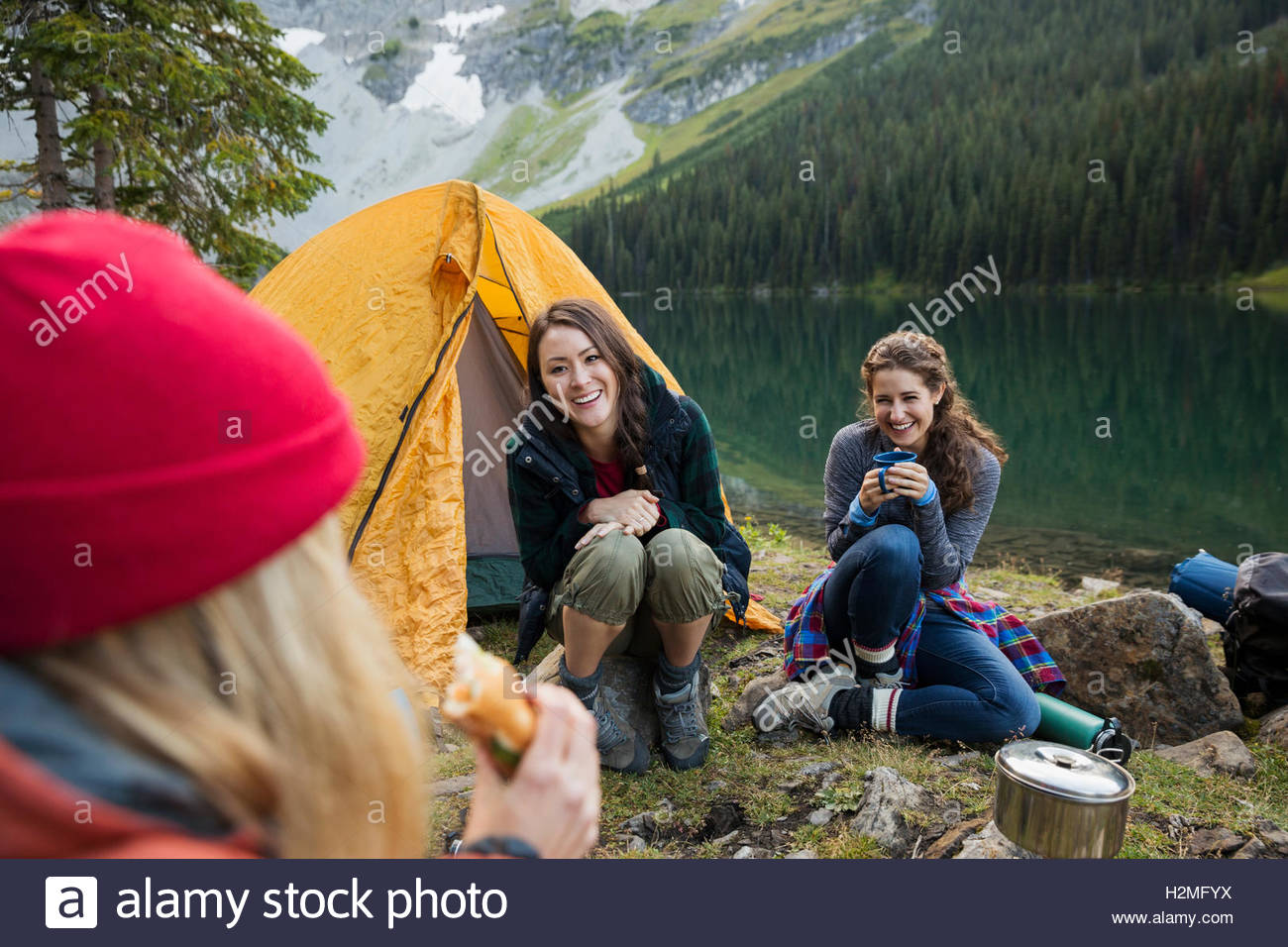 Female friends camping at remote lakeside campsite - Stock Image