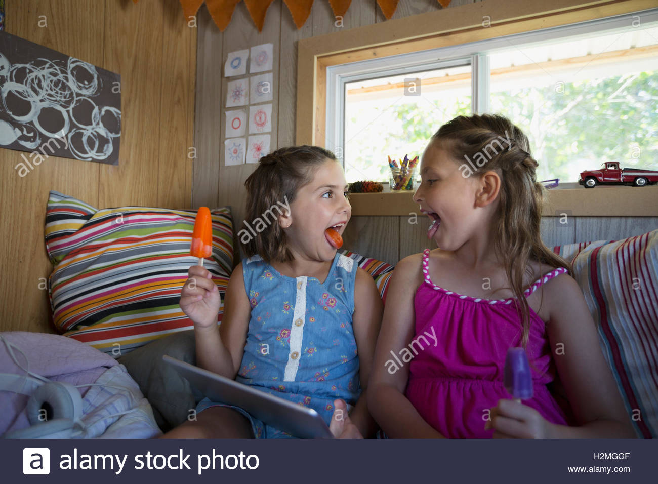 Girls showing purple and orange tongues from flavored ice in treehouse - Stock Image
