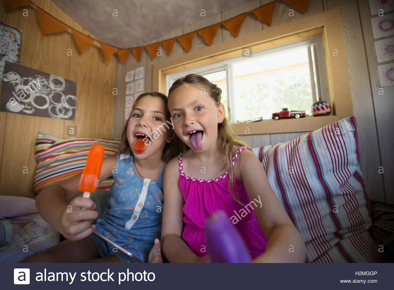 Portrait girls showing purple and orange tongues from flavored ice in treehouse - Stock Image