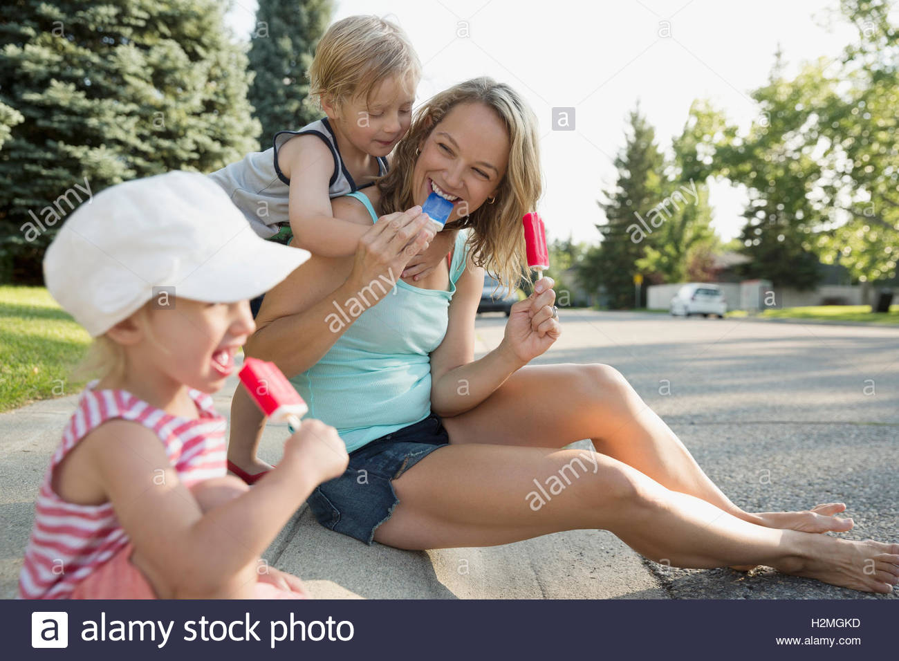 Family eating flavored ice on curb - Stock Image