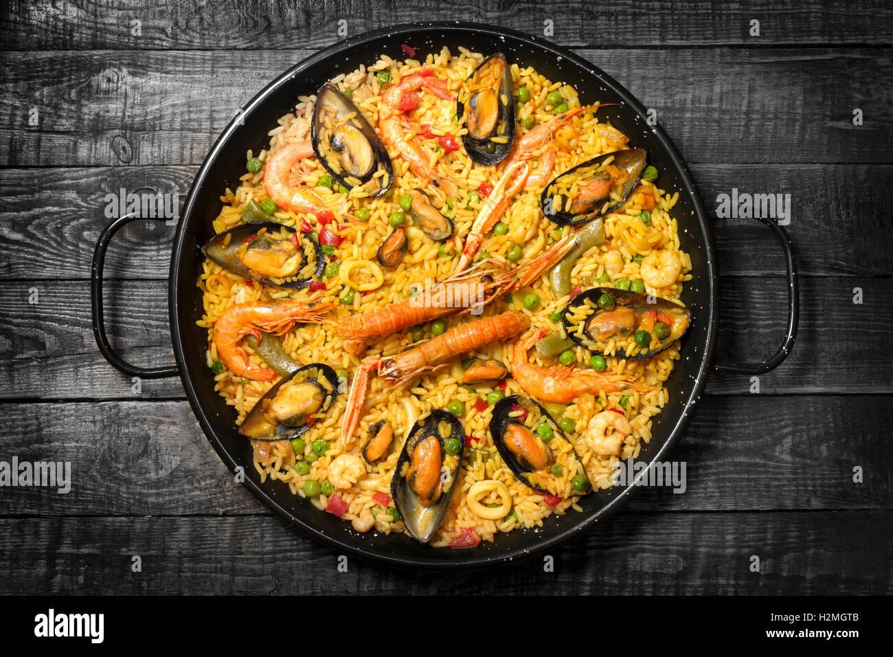 Spanish paella on a dark wooden table Stock Photo