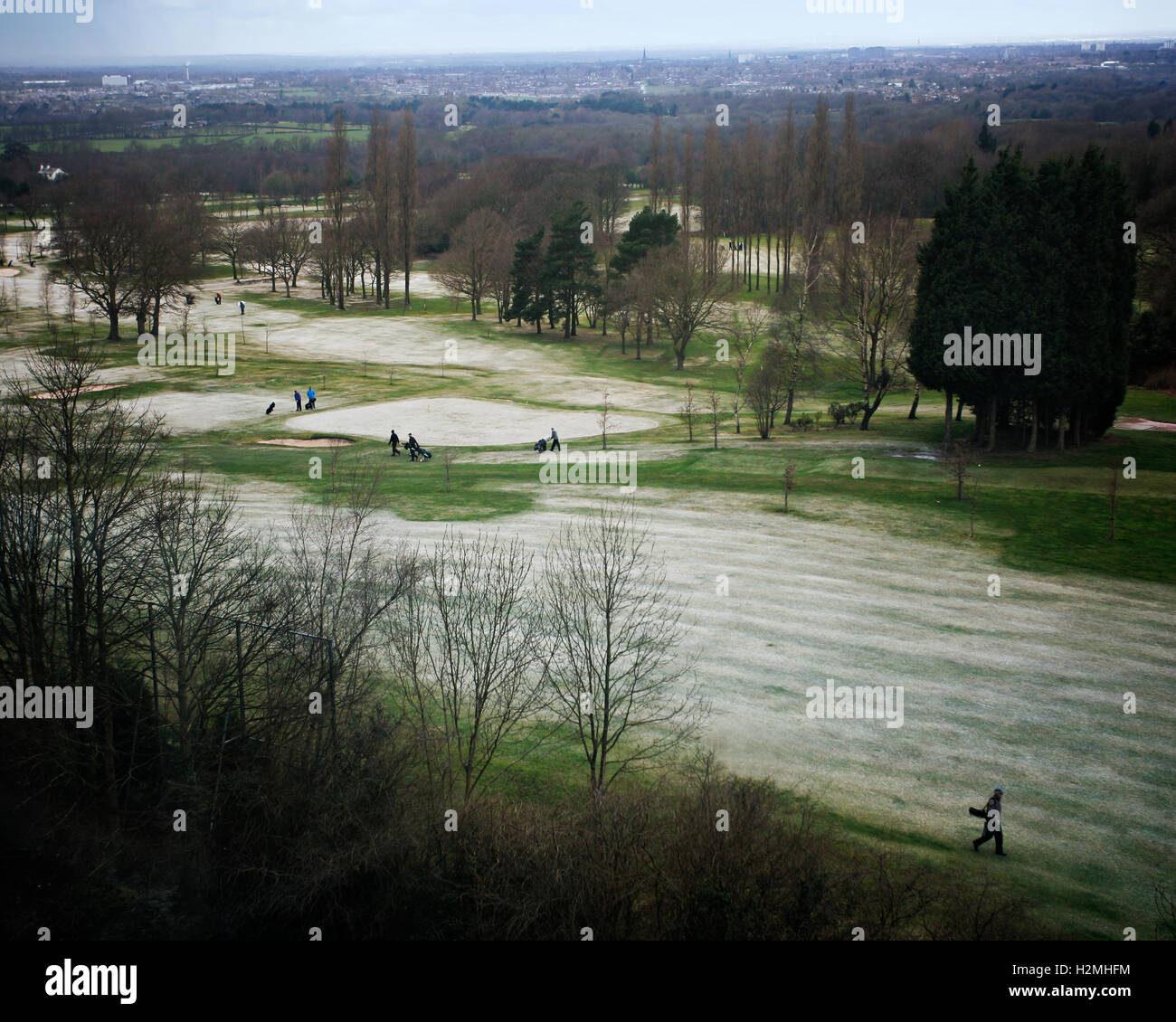 Golfers walking on frosty golf course - Stock Image