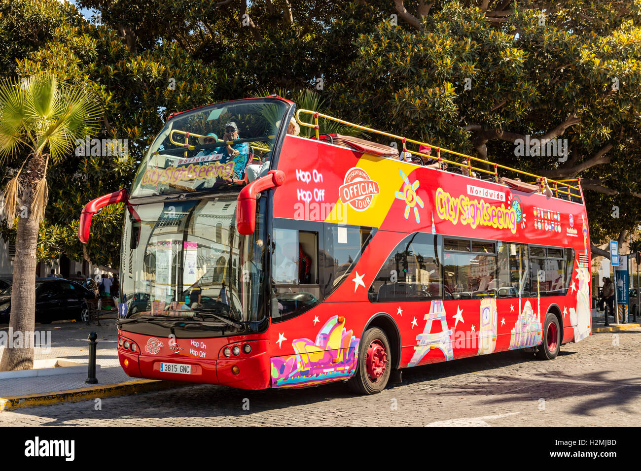 Brightly decorated sightseeing double-decker open top bus in Cadiz takes visitors to all the major tourist attractions. - Stock Image