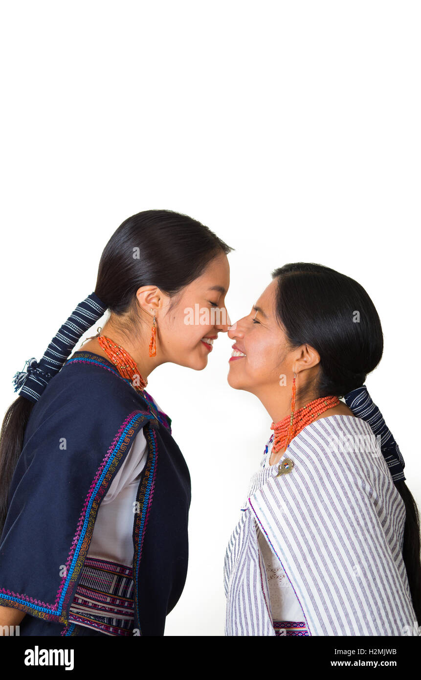 Beautiful hispanic mother and daughter wearing traditional andean clothing, seen from profile angle facing each Stock Photo