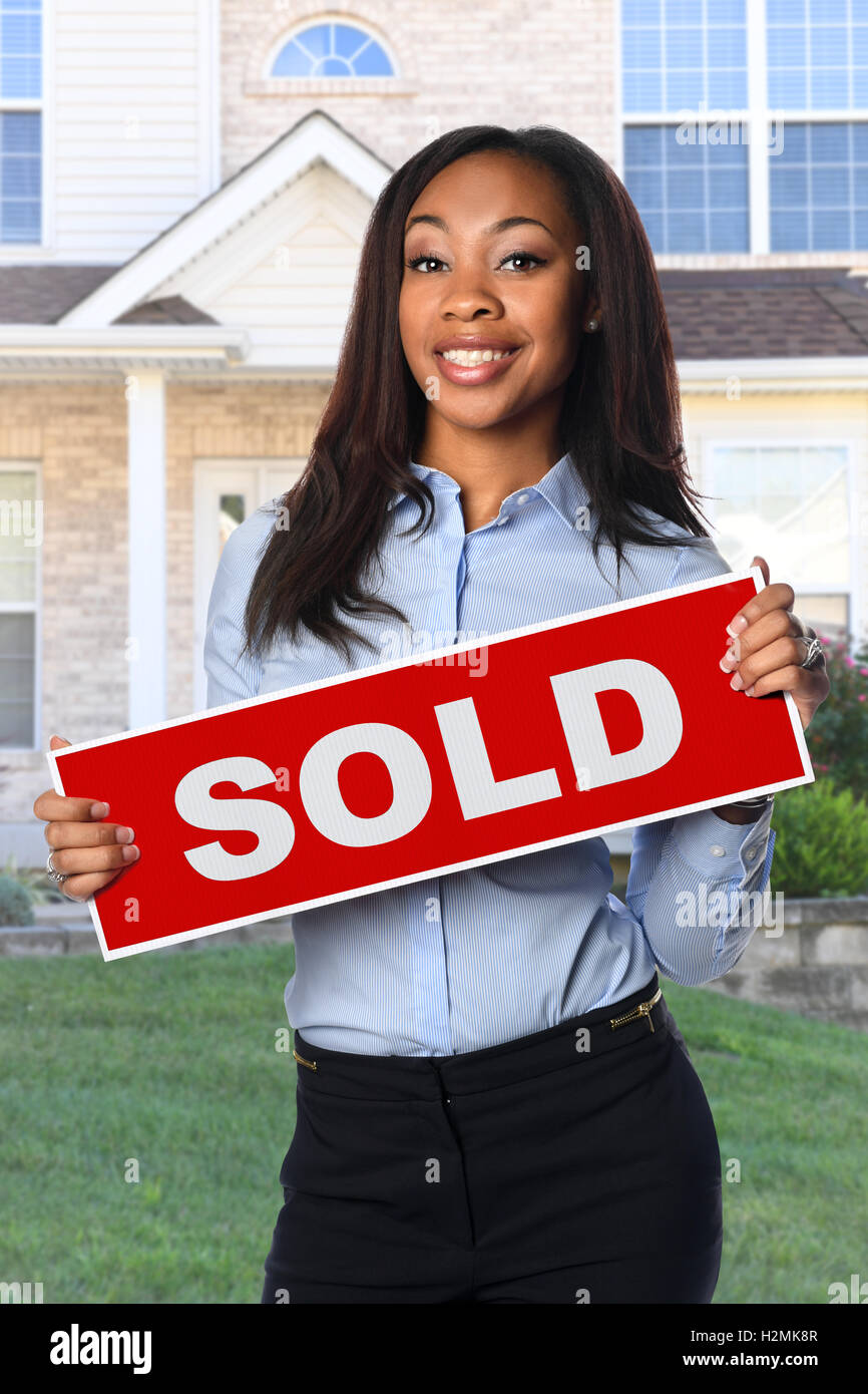 African American woman holding Sold sign in front of house - Stock Image