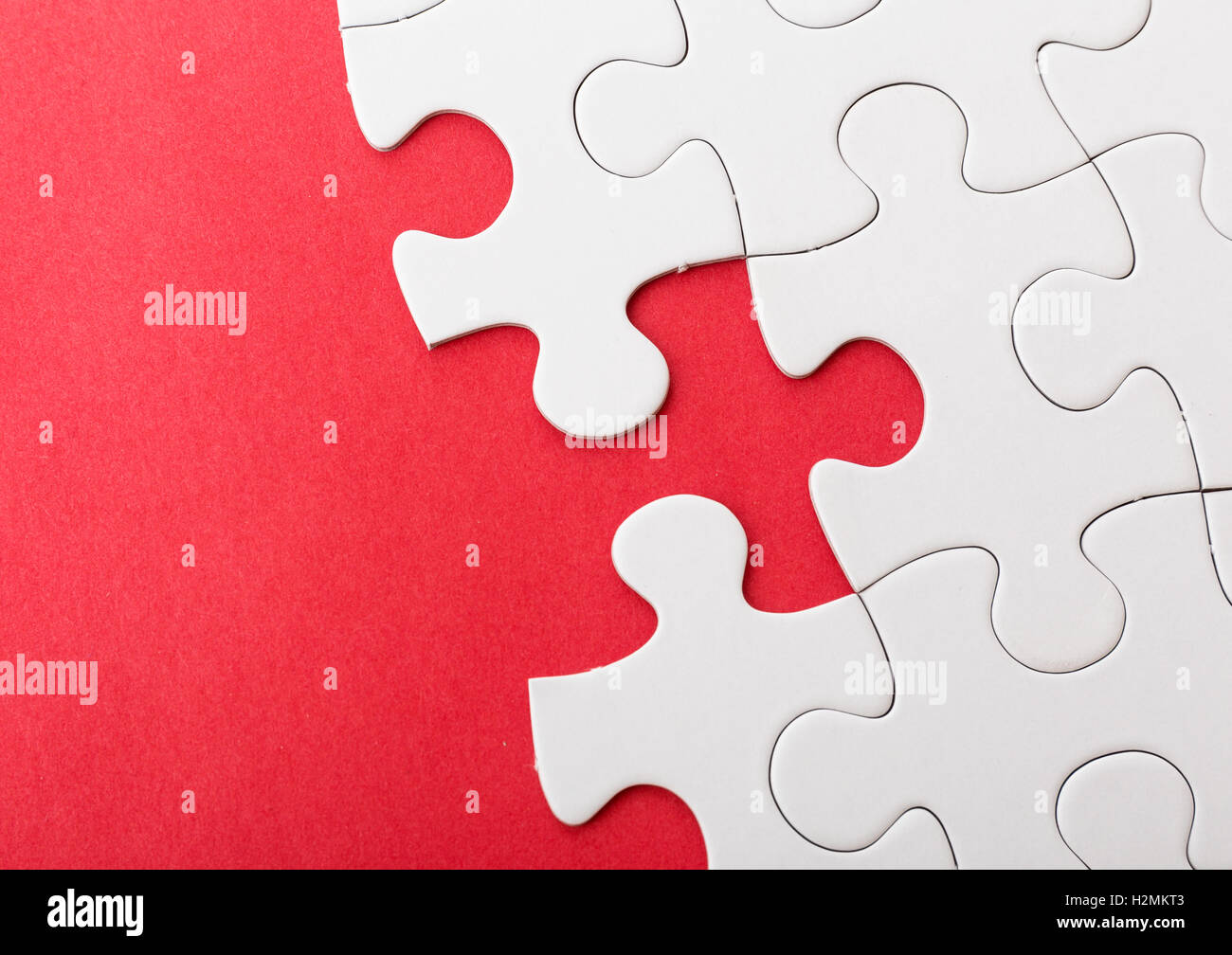 Incompleted white puzzle with red background Stock Photo