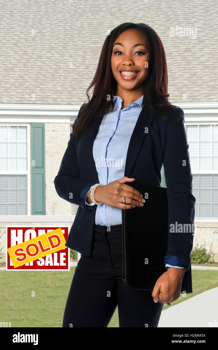 Young African American businesswoman smiling in front of sold home - Stock Image