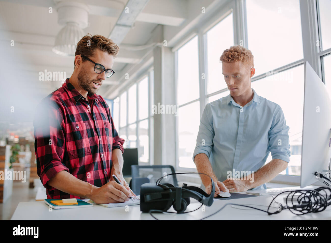 Two young businessman working together. They are standing at a table with virtual reality glasses. One using computer - Stock Image