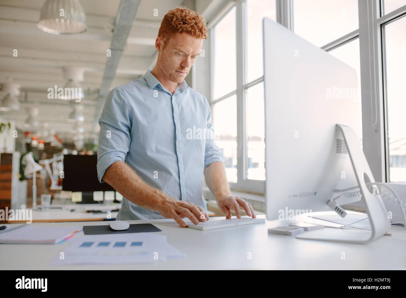Shot of young man standing at his desk and working on computer. Businessman working in modern office. - Stock Image