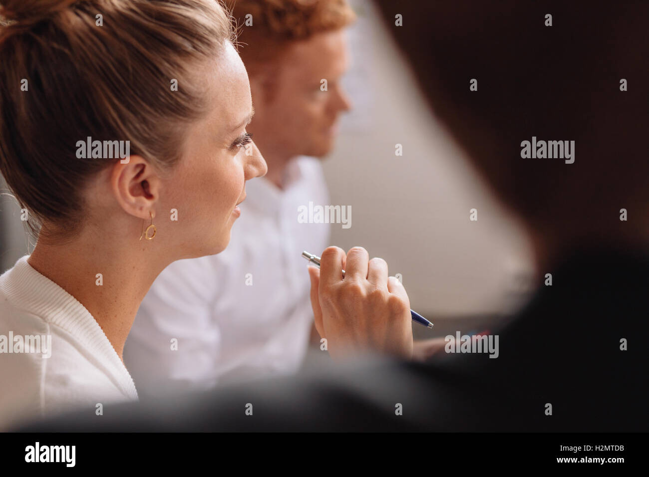 Close up shot of  young female listening to presentation in conference room. Businesspeople in a meeting in office. - Stock Image