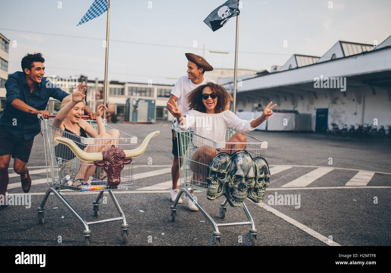 Young friends having fun on a shopping trolleys. Multiethnic young people racing on shopping cart. - Stock Image
