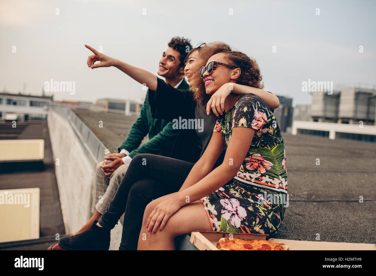 Man and women sitting on roof terrace and looking away smiling. Happy young friends relaxing on rooftop, with woman - Stock Image