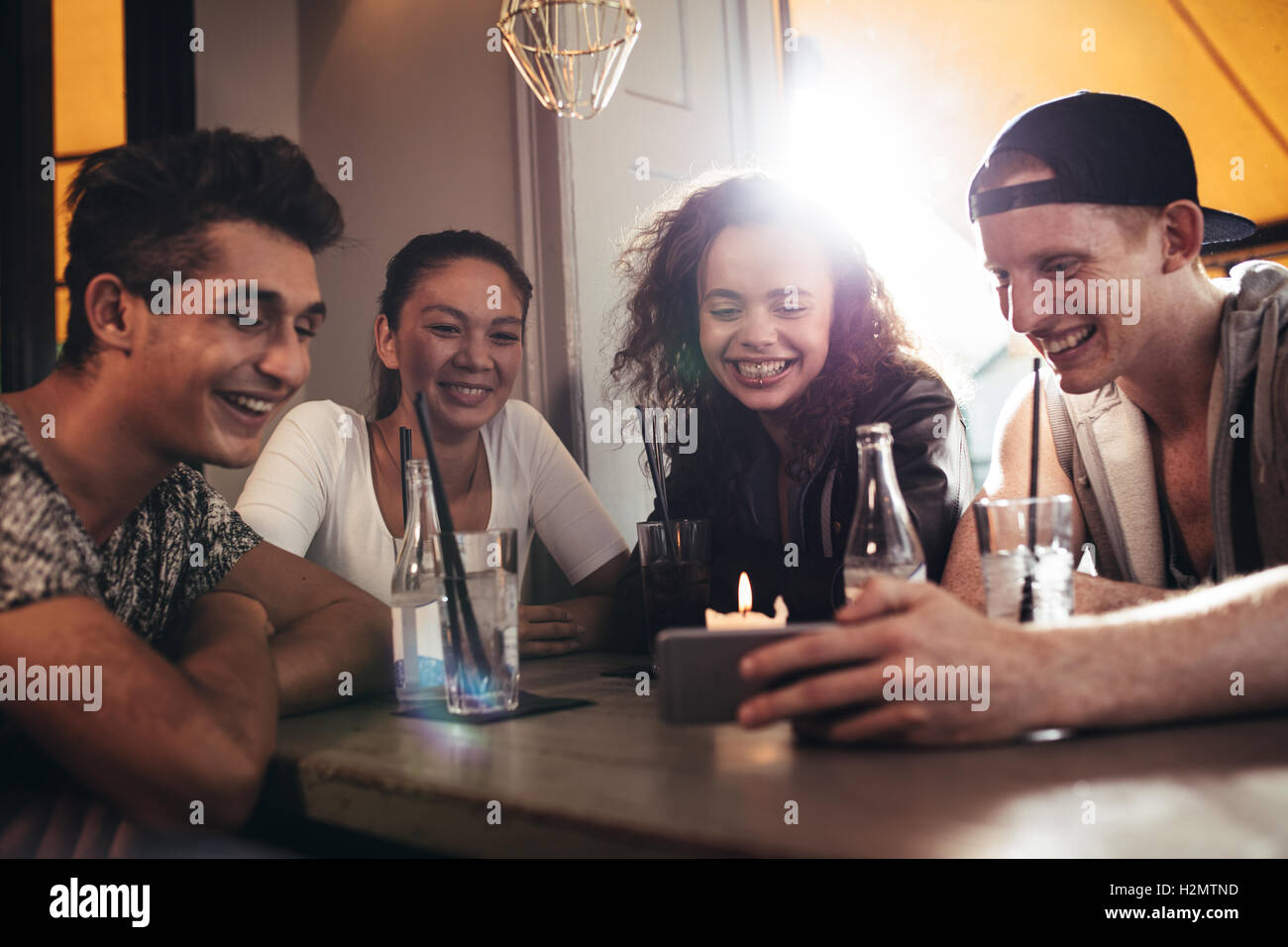 Group of friends sitting together in a cafe looking at mobile phone and smiling. Young guy showing something to - Stock Image