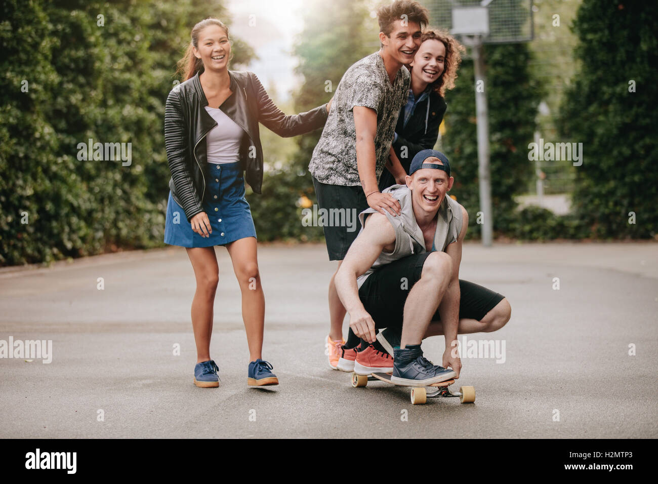 Full length shot of teenage guys on skateboard with girls. Diverse group of friends having fun outdoors. - Stock Image