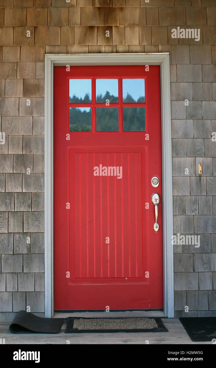 Red door at beach cabin, shake siding, windows at top of door, nice hardware on door handle, striking, relaxing, - Stock Image