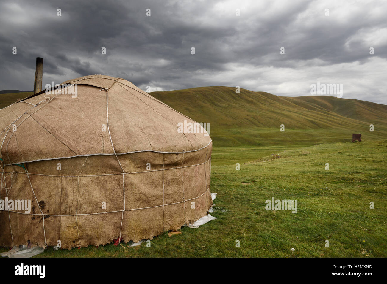 Yurt with chimney and outhouse in barren pastureland of Assy Plateau Kazakhstan Stock Photo