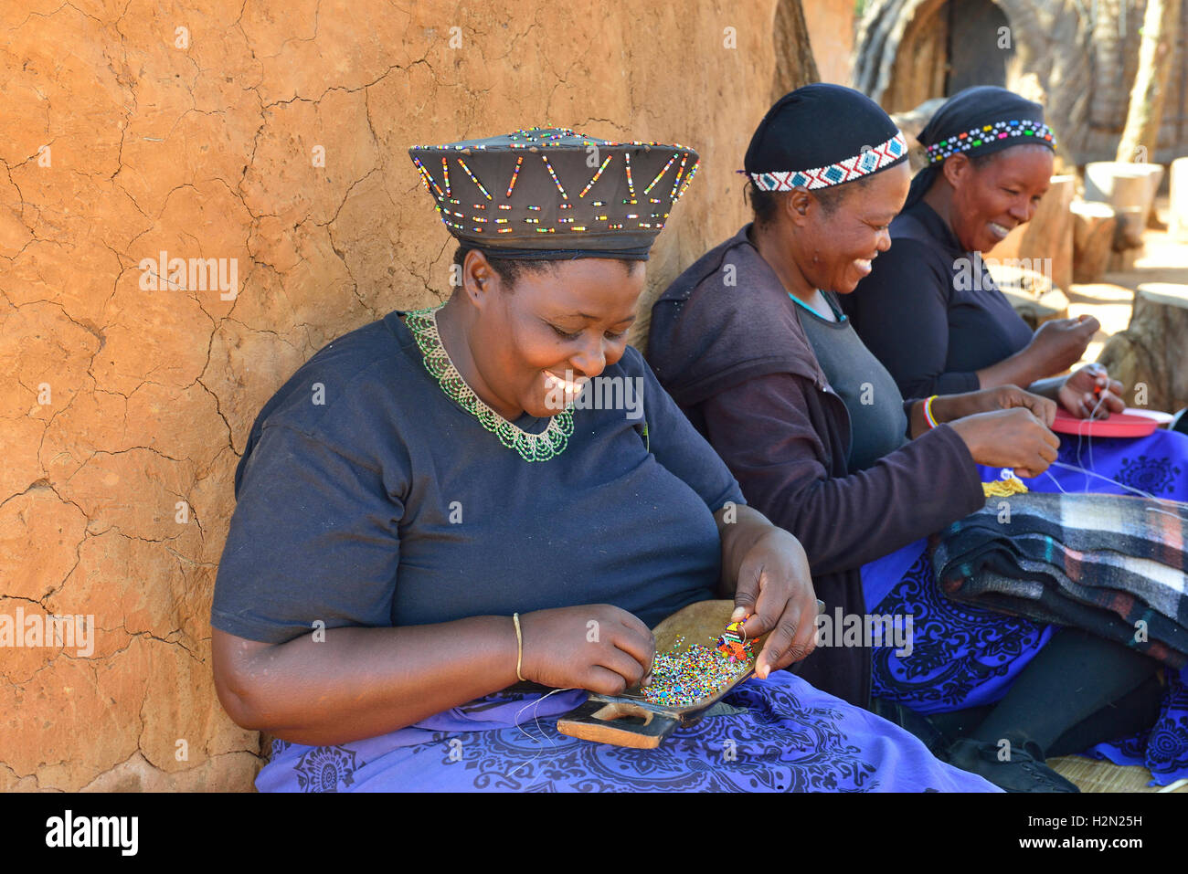 Zulu women making traditional beaded decorations at Shakaland Cultural Village, whilst seeking the shade from a - Stock Image