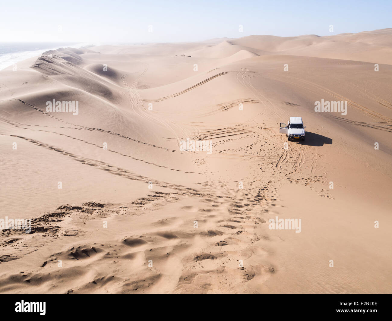 A four by four car on the dunes of the Namib Desert in Sandwich Harbour, Namibia. Horizontal orientation, wide angle. - Stock Image