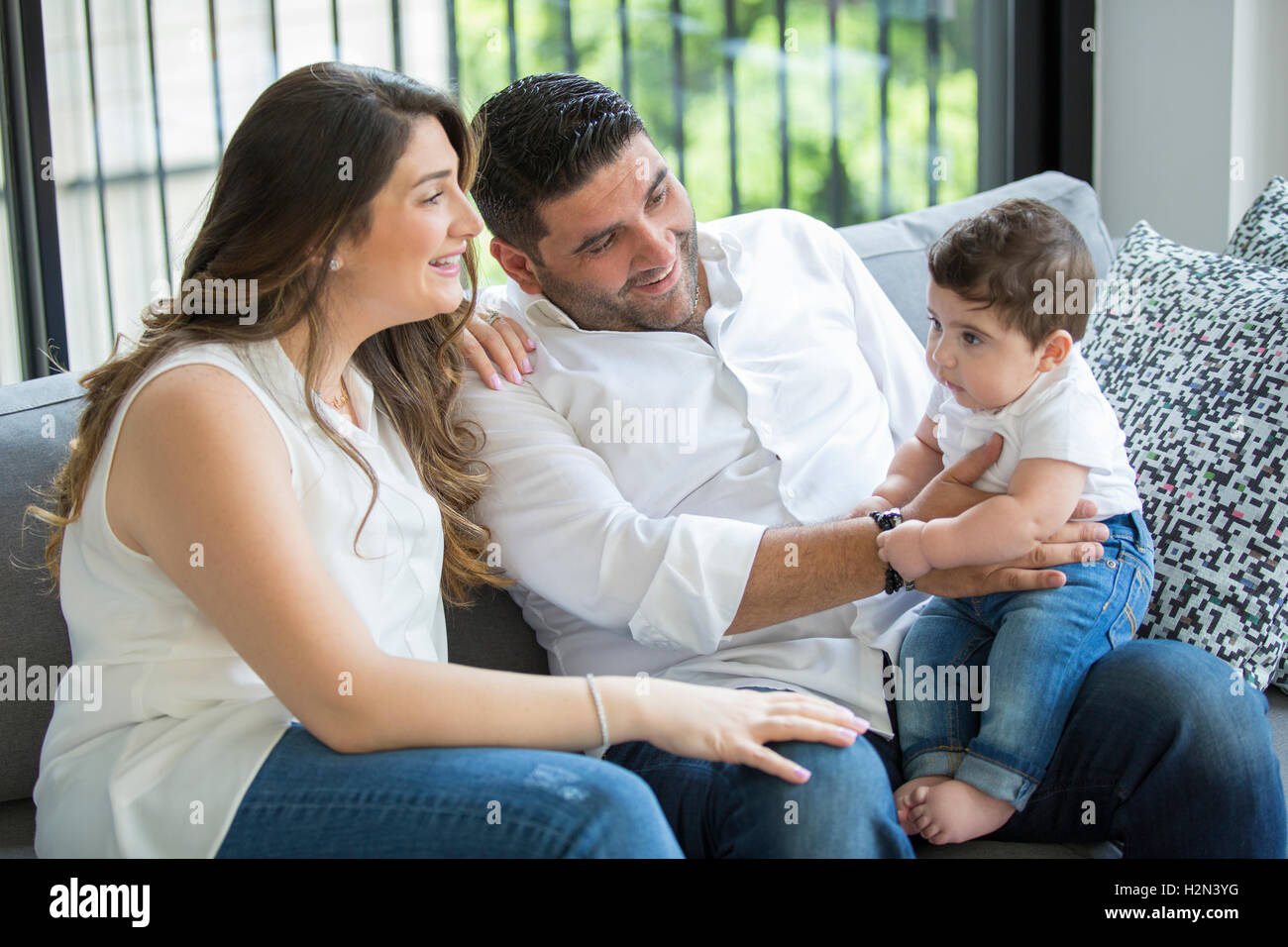 Father and mother with their baby boy sitting indoors smiling - Stock Image