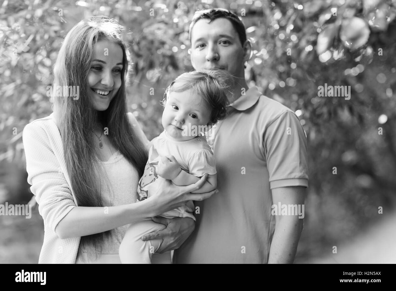happy couple with daughter in park, black - white photo - Stock Image