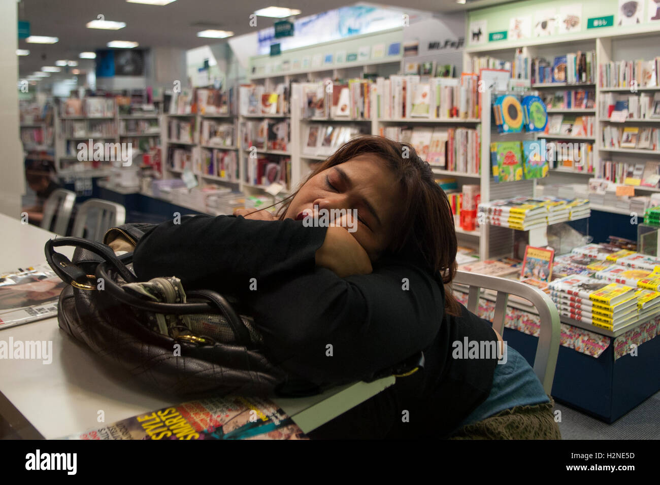 Young woman sleeping in a book store in Roppongi Hills central Tokyo Japan - Stock Image
