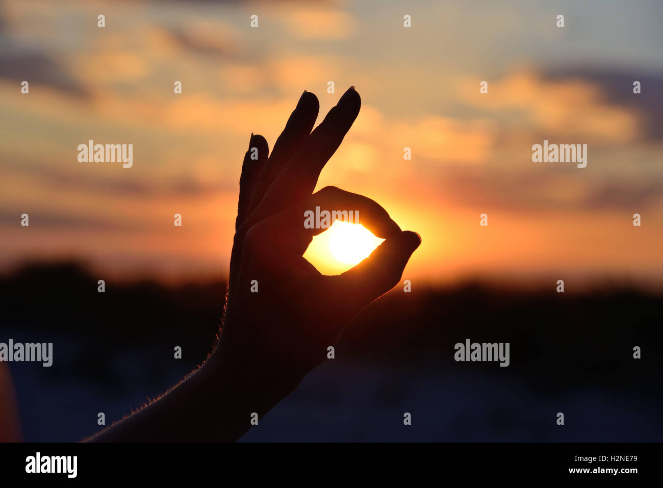 okay gesture on the background of the sun - Stock Image