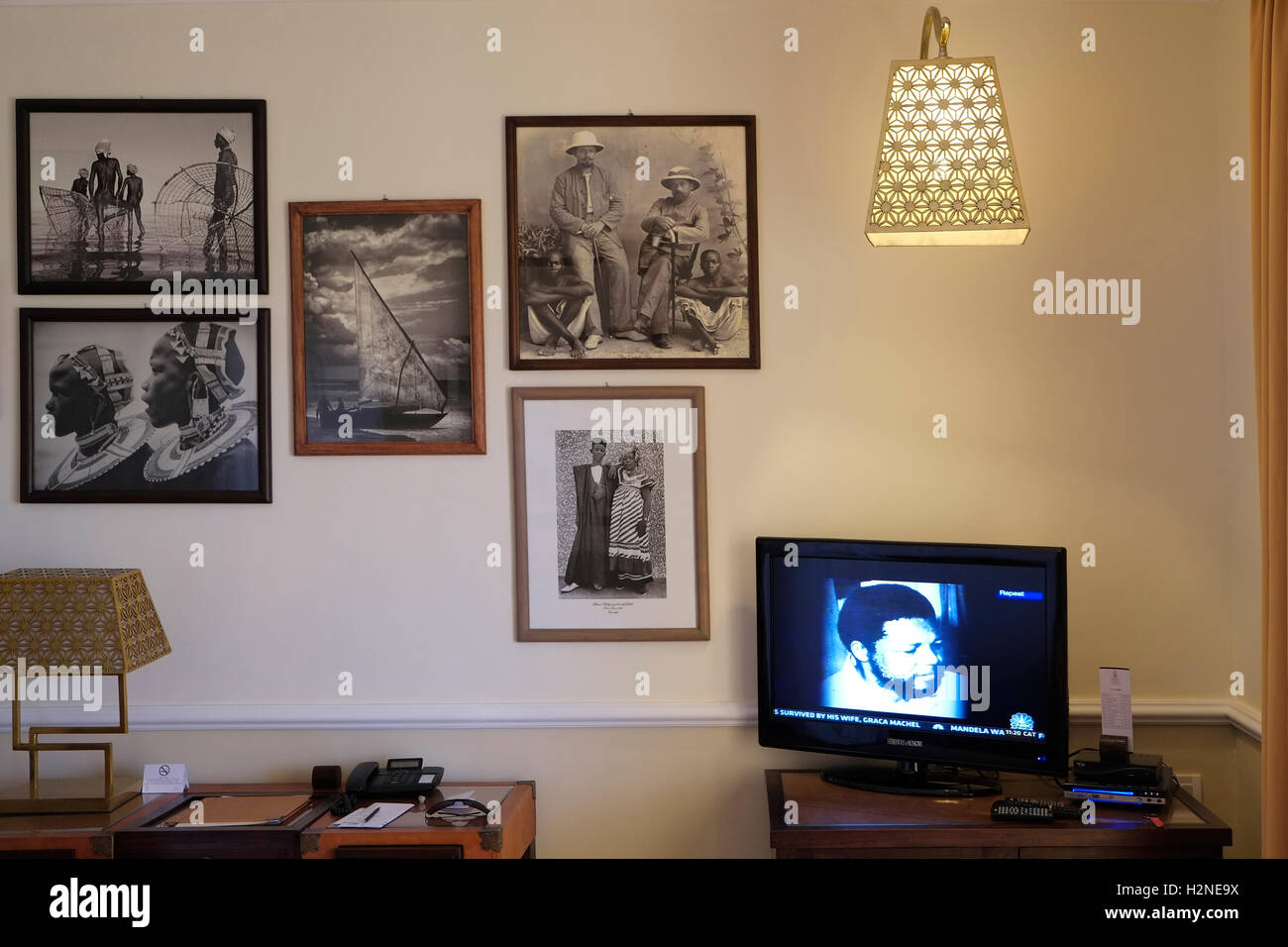 A film about Nelson Mandela is seen in a TV monitor in a room decorated with colonialist old photographs in Hideaway - Stock Image
