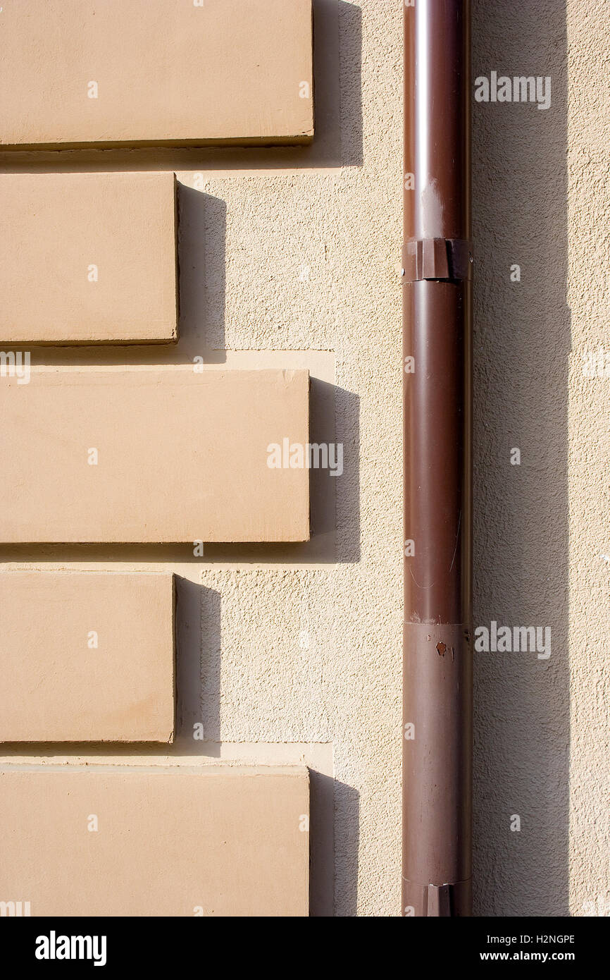 Brown drainpipe (downspout, downtake tube, drainage pipe, rain pipe, storm water pipe) with a wall pattern on a - Stock Image