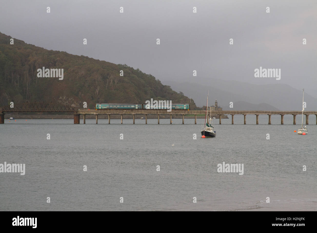 Arriva Trains Wales ATW service train crosses Barmouth Bridge, the Network Rail infrastructure wooden viaduct over Stock Photo