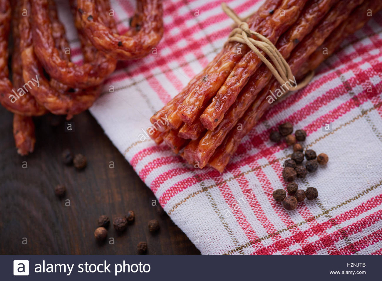 Sausage or kabanos and pepper on vintage wooden boards - Stock Image