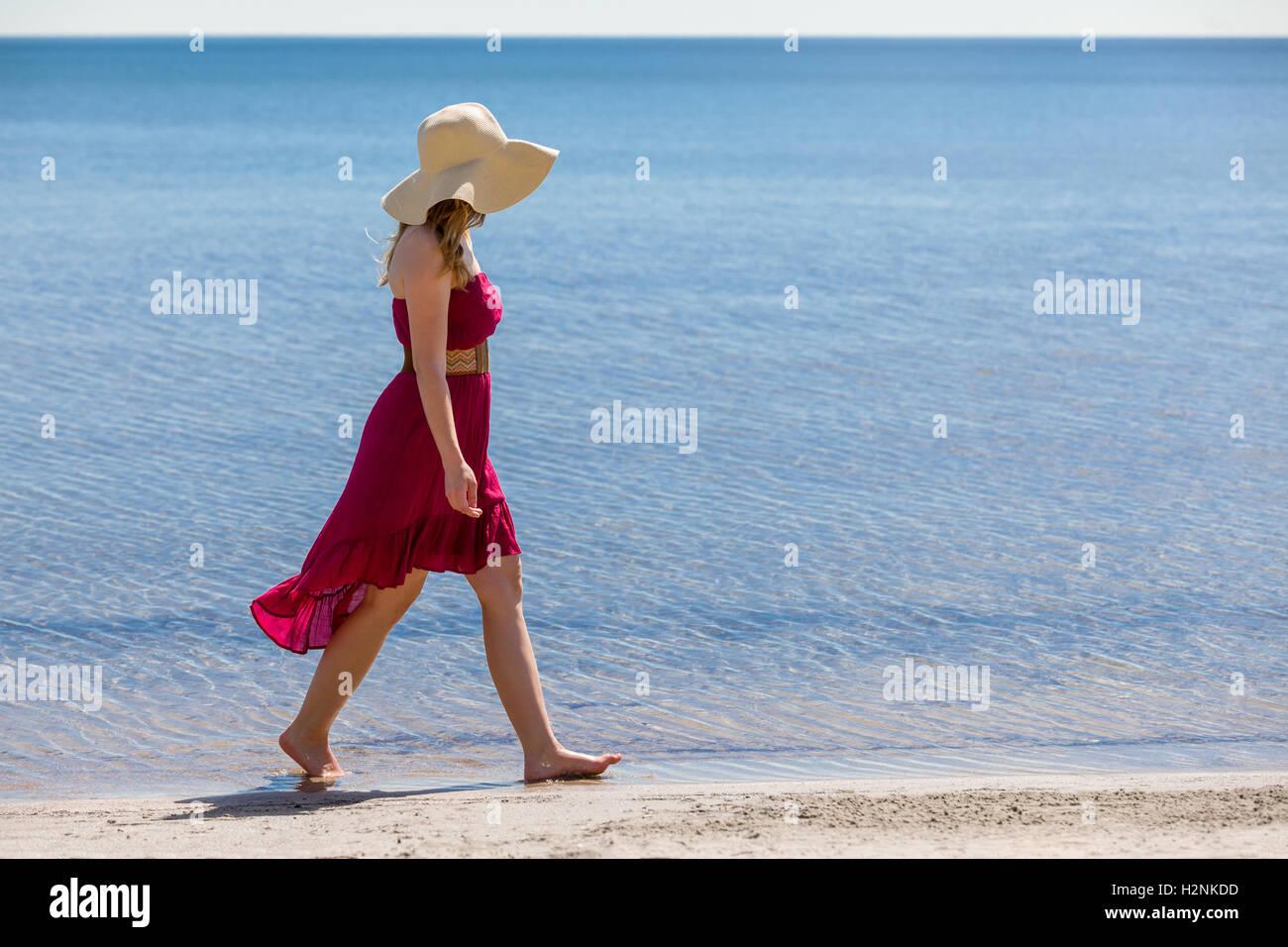 6979b37402 Beautiful woman with a red sun-dress walking along the beach Stock ...