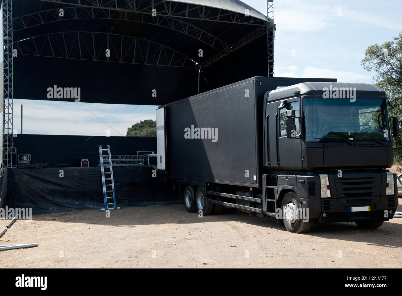 Truck near a concert stage starting setting it up - Stock Image
