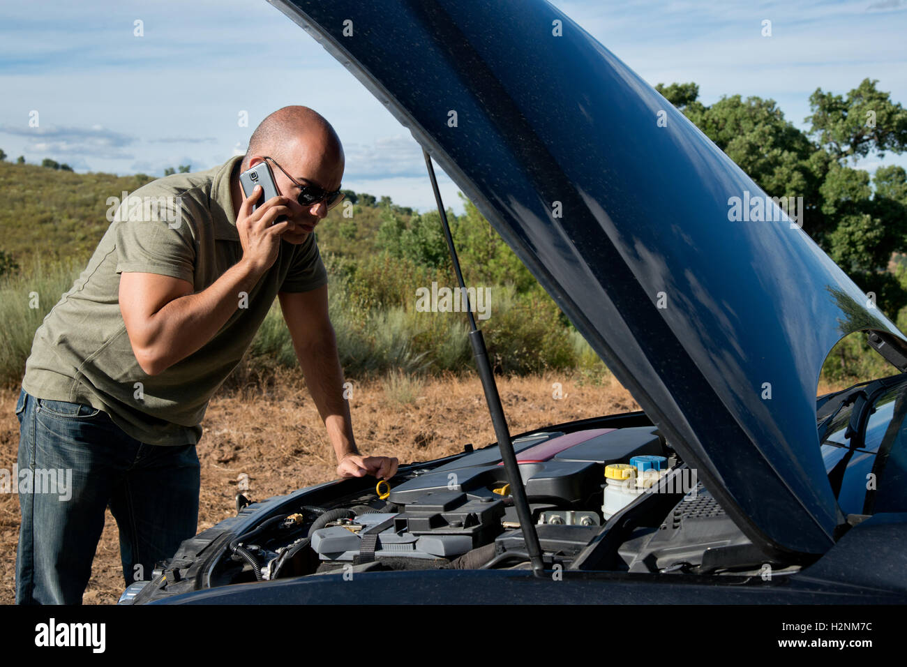 Close up of a broken down car, engine open, in a rural area and the driver looking at the engine - Stock Image