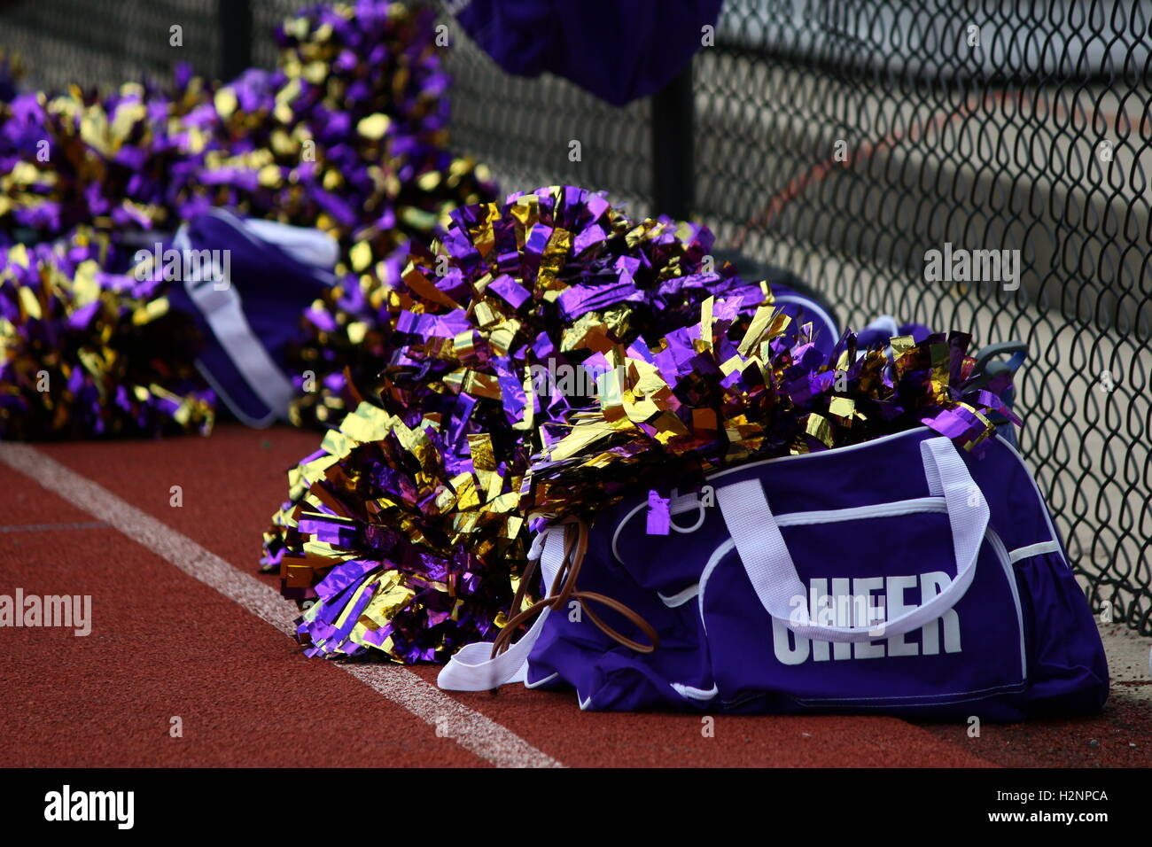 Cheerleader Bags And Pom Poms By Fenceline On Tennis Court Stock Image